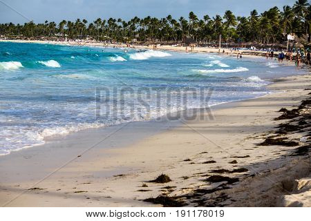 Punta Cana, Dominican Republic - July 03, 2016: Tropical white sandy beach with palm trees. Punta Cana, what's known as La Costa del Coco, or the Coconut Coast, an area of nice, all-inclusive resorts.