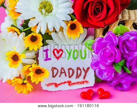 Father's day concept. I LOVE YOU DADDY message with white and yellow flower two red heart and black Mustache on pink background