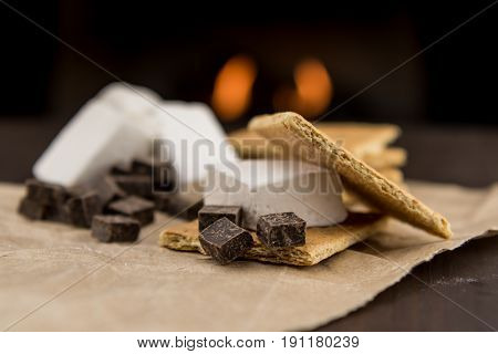 Smore Ingredients with Fireplace in BackGround over brown paper