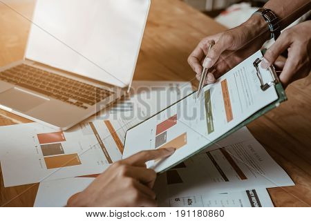 Businessman using pen pointing graph chart with pathner for analyze plans in this mounth.