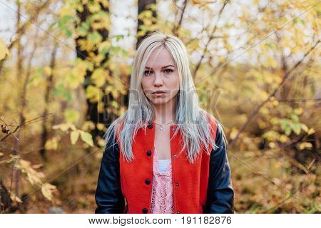 Portrait of a beautiful yung woman in bomber jacket in autumn forest.