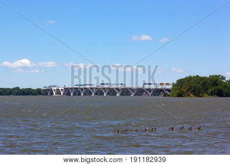 Woodrow Wilson Memorial Bridge across Potomac River photographed from the National Harbor Maryland USA. City infrastructure and nature on a summer day.