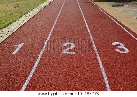 Red treadmill track running at the stadium with green grass