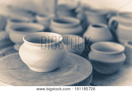Old vintage photo. many clay pot is on the table in pottery. Copy spase