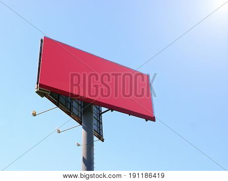 Wide red background with backlighting large empty billboard, against a blue sky background illuminated by the sun