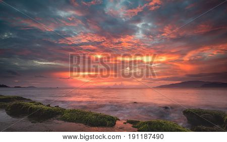 Looking out over the south china sea, Nha Trang bay just after sunrise with a colourful cloudy sky and moss covered rocks in the foreground.