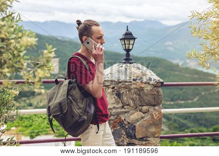 Man Traveler With Backpack Talking On The Phone On A Background Of Mountains
