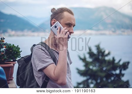 Man Traveler With Backpack Talking On The Phone On Background Of The City.