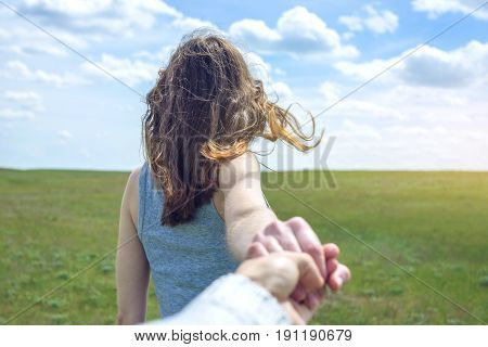 Follow Me, Attractive Brunette Girl Holding The Hand Of The Leads In A Clean Green Field, Steppe Wit