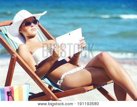 Young, attractive woman in sexy swimsuit relaxing on beach. Traveling, resort, vacation concept.