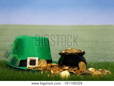 Pot of gold spilling over onto green grass Leprechaun hat laying next to it green grass field off to the skyline. Copy space