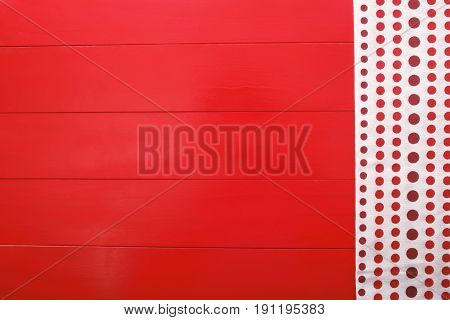 A red wooden board with polkadot napkin