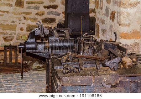 Old workbench with various tools and machines.