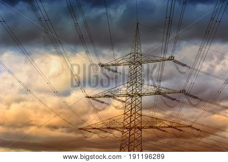 Electricity mast or also high voltage line in the background a cloudy sky.