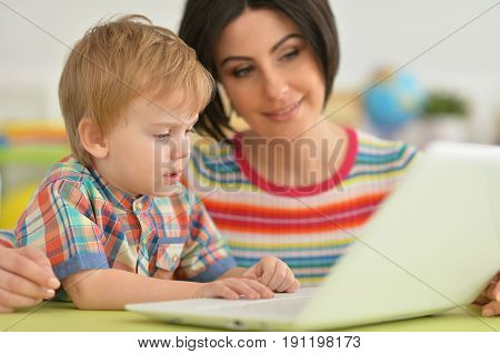 Mother and son sitting at table and using modern laptop