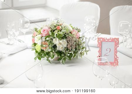 table setting, festive round tables ready for guests. Beautifully organized event. floral arrangement in the center. fresh flowers cut-off