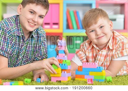 two brothers playing with colorful plastic blocks in room