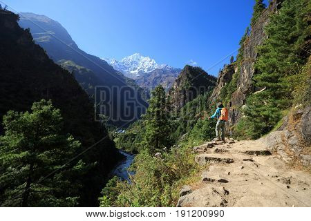 Young woman backpacker trekking at the himalaya mountains