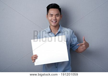 Waist-up portrait of smiling Asian man posing for photography while holding blank sheet of paper in hands, studio shot