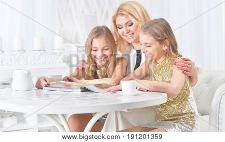 Portrait of a mother with her twin daughters reading a magazine