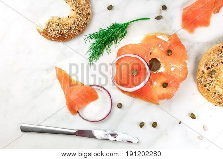 Bagel ingredients. Lox, purple onions, capers, dill, and the buns, shot from above on a white marble background in the process of making, with a place for text