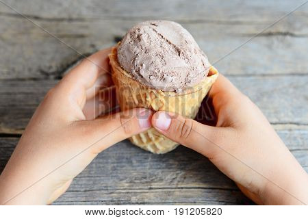 Small kid holds ice cream in his hands. Kid eats ice cream. Chocolate ice cream in a waffle cup. Vintage wooden background