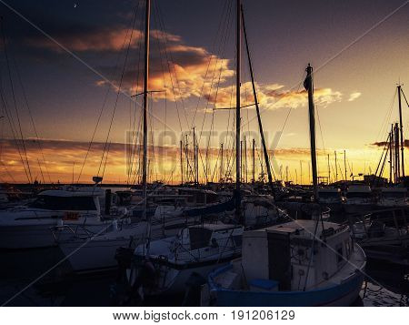 Boats in port at sunset. Cruise ships anchored in harbour..