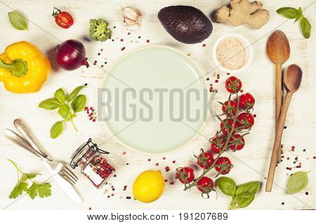 Fresh raw greens and unprocessed vegetables over rustic white background, blue plate in center, top view, copy space. Healthy, clean eating, vegan, detox, dieting food concept