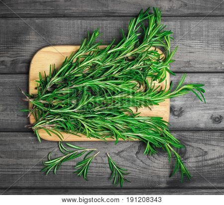 Branches of rosemary on gray wooden table. Rosemary on cutting board. Rustic style fresh organic herbs. Top view blank space.