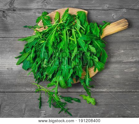 Fresh arugula leaves on wooden board rucola. Arugula rucola on gray old background. Top view blank space.