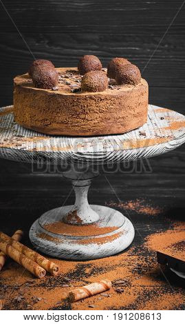 Chocolate cake torte covered with cocoa powder and decorated with truffle. Ingredients for Chocolate cake torte Chocolate waffles sticks truffles and Chocolate bars. Dark black wooden background.
