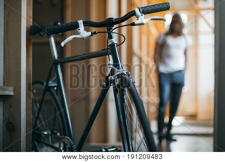 Close-up View Of Black Hipster Bicycle And Man Walking Behind