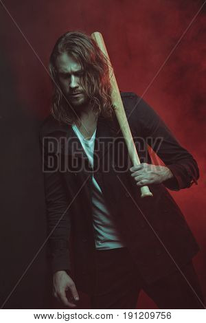 Serious Long Haired Man Holding Baseball Bat On Shoulder And Looking Down