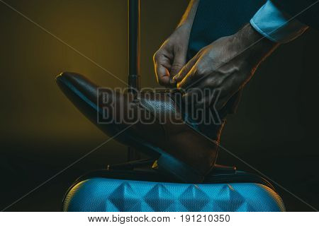 cropped shot of stylish man tying shoelaces on suitcase