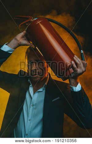 Frightened Caucasian Man In Suit Holding Fire Extinguisher