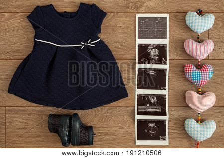 Flat lay of navy blue dress and matching boots of infant baby girl beside sonography pictures and colorful cotton hearts on wooden surface.