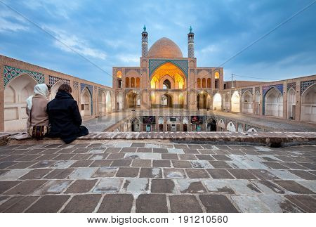 KASHAN IRAN - March 08 2017: Young couple visiting Agha Bozorg Mosque as tourists. This Mosque was constructed for prayers and theological sessions held by Molla Mahdi Naraghi known as Agha Bozorg.