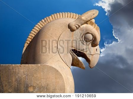 Statue of Huma or Homa bird as decorative column capital in Persepolis of Shiraz against blue sky with white clouds.