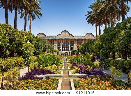 SHIRAZ, IRAN - SEPTEMBER 18, 2014: People visiting Persian garden of Narenjestan-e Ghavam and its historic pavilion. This garden is a landmark of Shiraz and very popular among tourists.