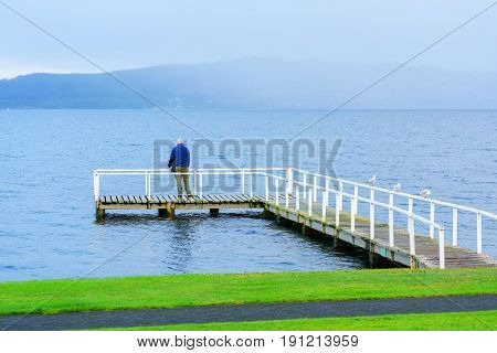 TAUPO , NEW  ZEALAND - APRIL 14 , 2017 : Senior man standing on the bridge admiring the beauty of Lake Taupo in the morning , South Island of New Zealand