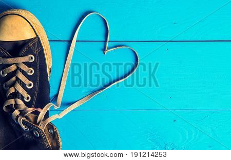 Dirty gumshoes on Heart wooden background at Thailand