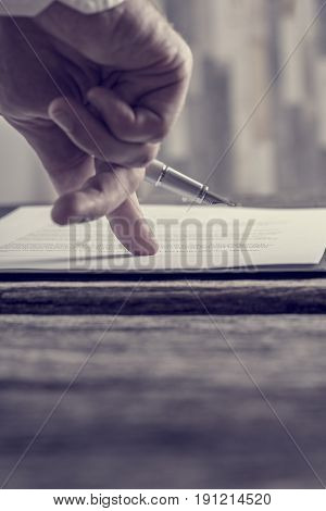 Retro effect faded and toned image of a businessman hand pointing with his finger where to sign a contract or document or sign a subscription papers.