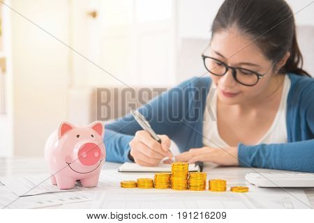 Woman Counting And Recording Her Savings