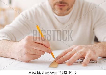 Straight line. Attentive male person pressing lips and holding pencil in right hand while making changes in his project