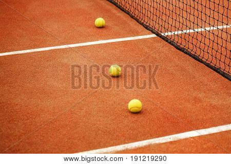 Three yellow tennis balls lie on the tennis court near the net. The concept of sport.