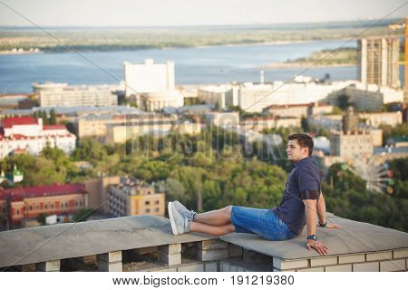 Roofer sits on the roof of a high-rise building and looks into the distance. Freedom and adrenaline.