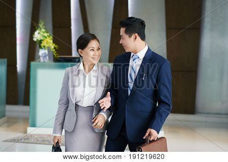 Smiling Asian colleagues in businesswear chatting animatedly with each other while standing in modern office lobby