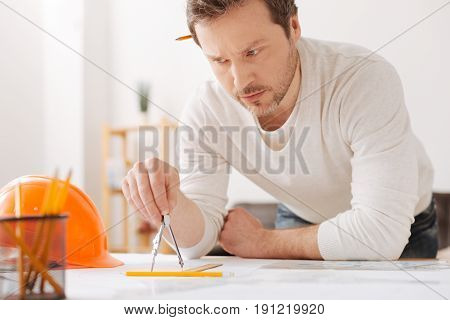 Draw a circle. Attentive bearded engineer holding special device in right hand leaning elbows on the table while looking at helmet