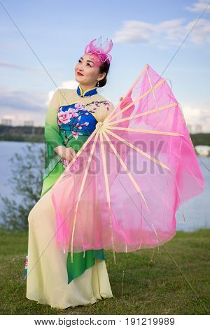 beautiful chinese girl in traditional chinese dress with fan on the riverbank