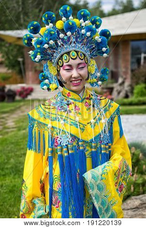 Beautiful Chinese Girl In Traditional Chinese Dress With Long Sleeves And Hat Standing Outdoor